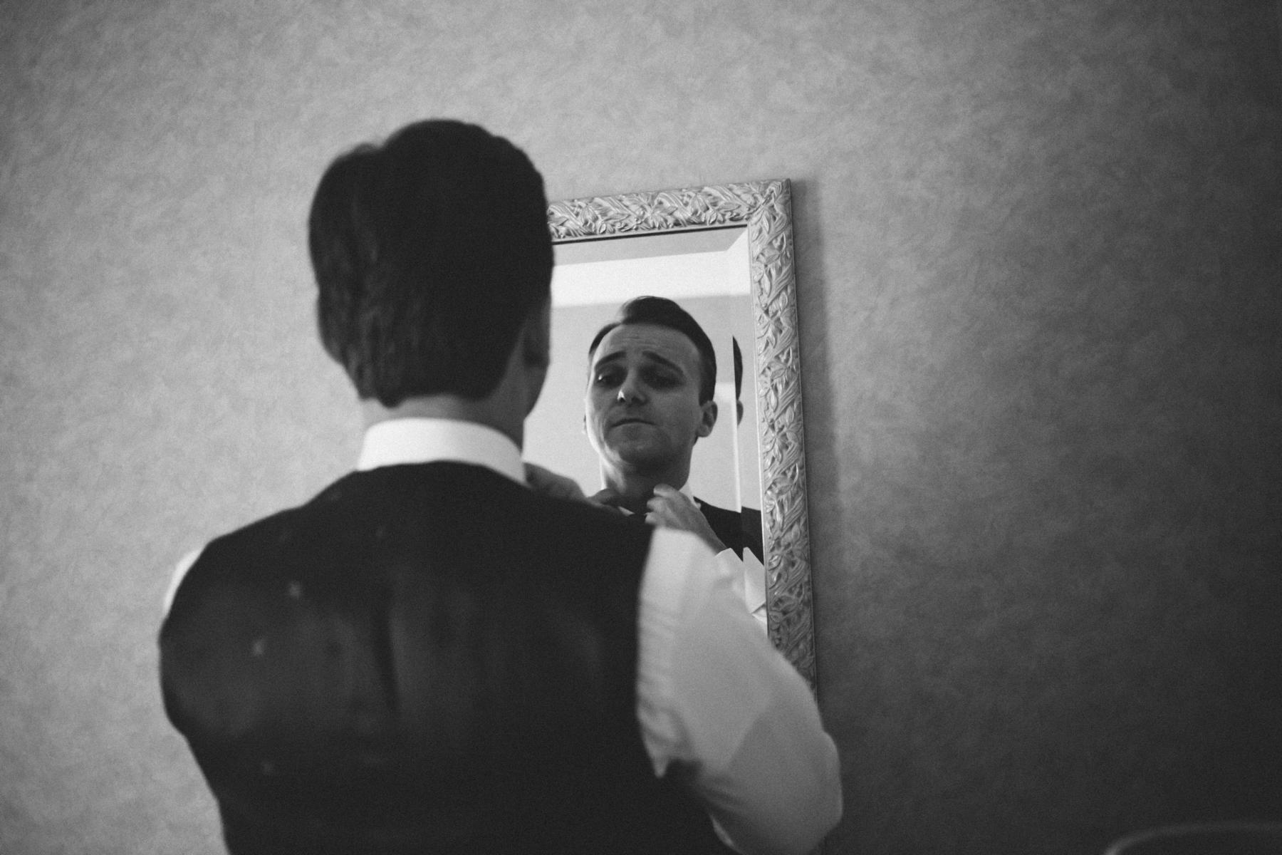 Bräutigam beim Getting Ready vor Spiegel
