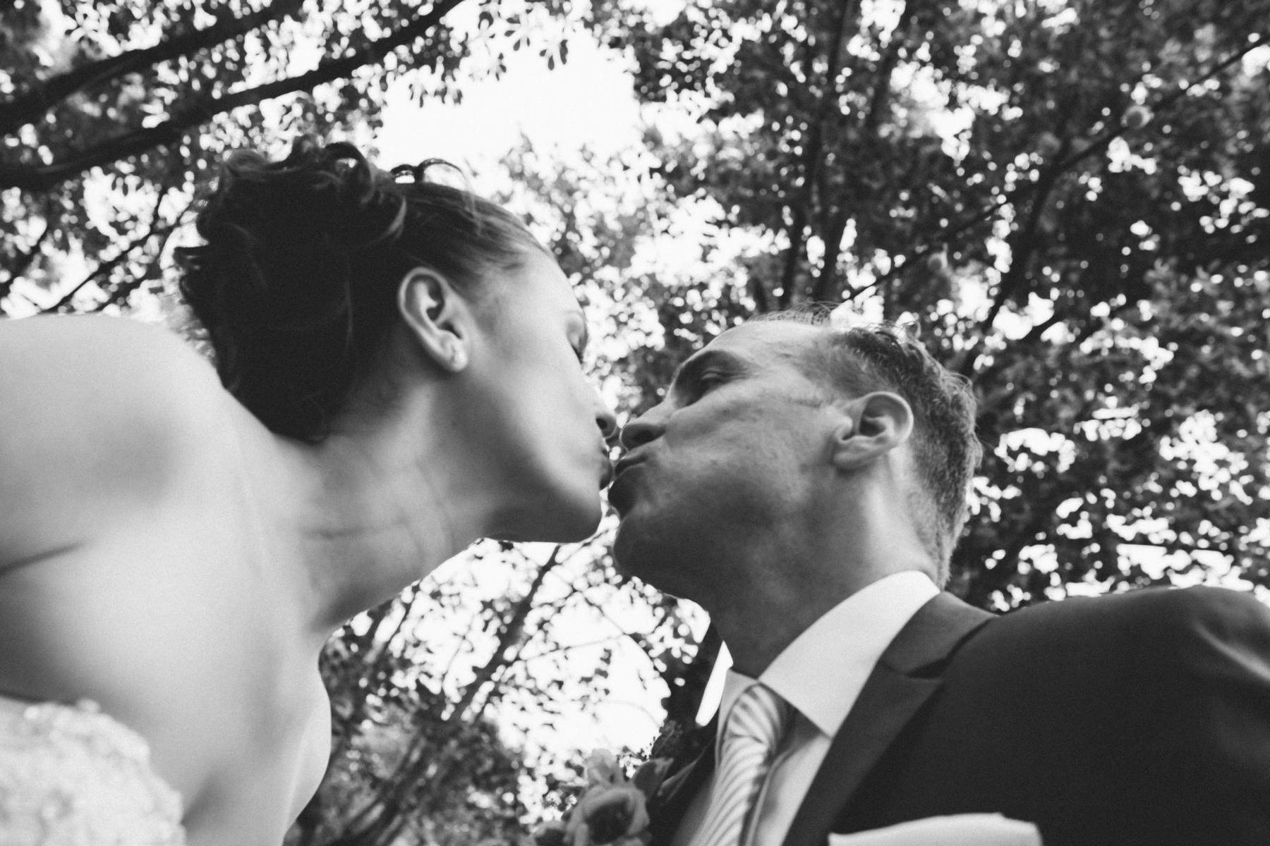 Braut küsst Bräutigam bei Hochzeitsfeier in der Lusie Dahlem in Berlin