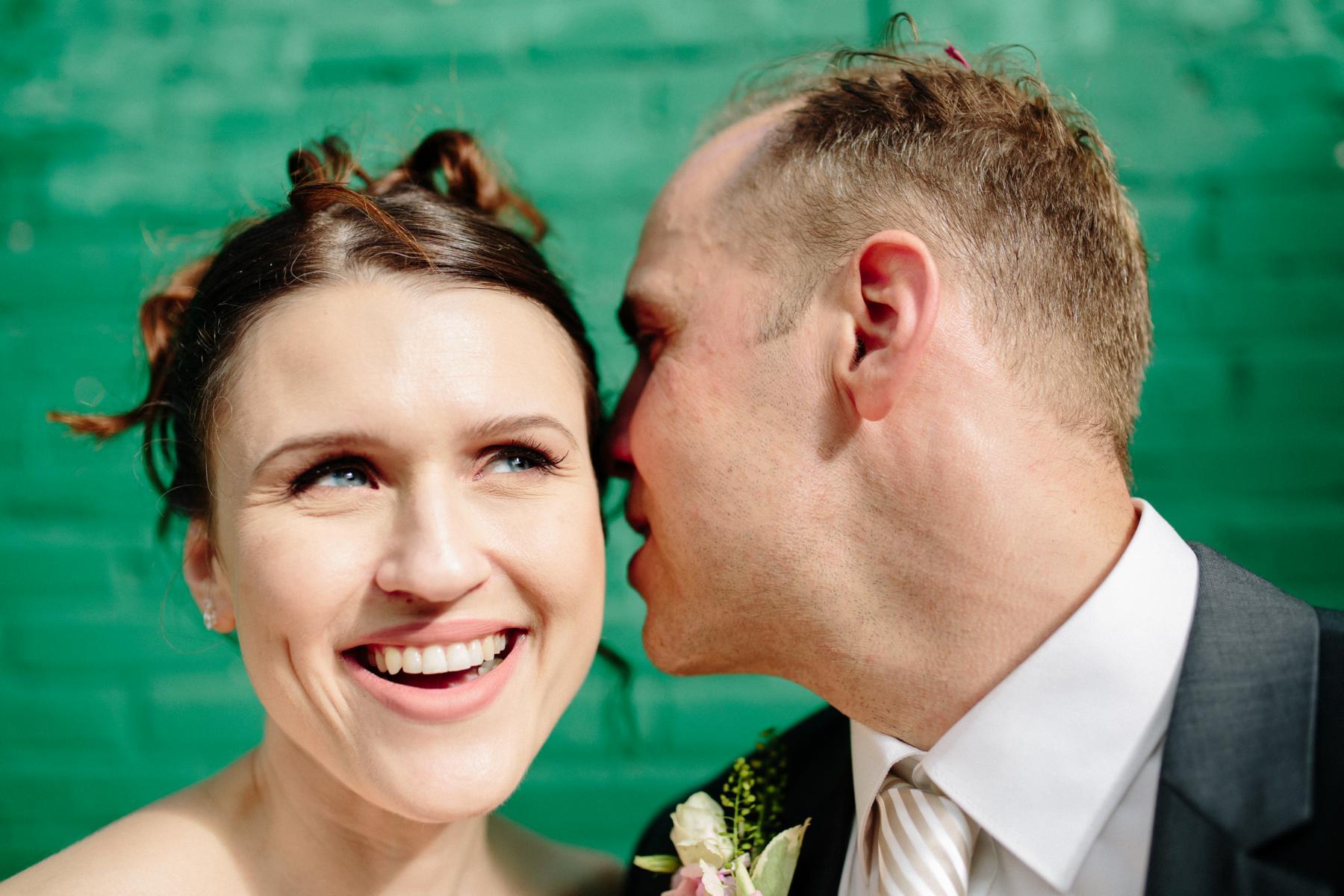 Bräutigam flüstert Braut beim Paarshooting in Berlin ins Ohr