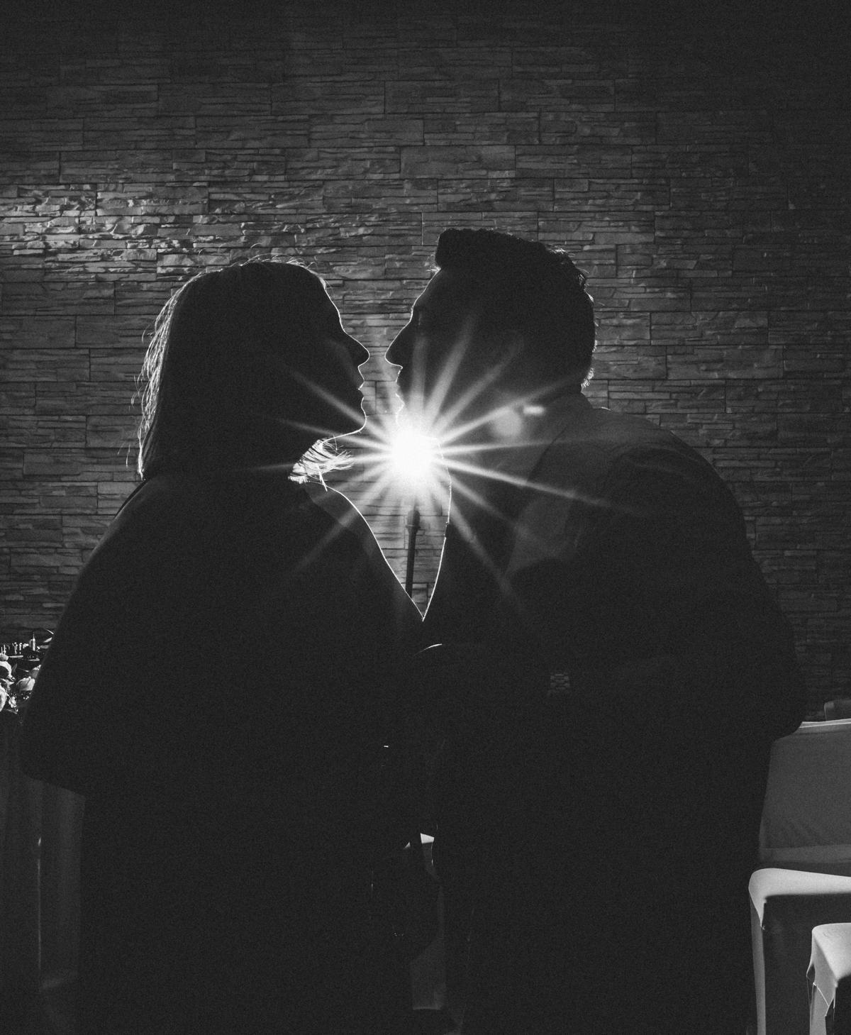 Hochzeitsgäste küssen sich im Blitzgegenlicht bei Hochzeitsfeier