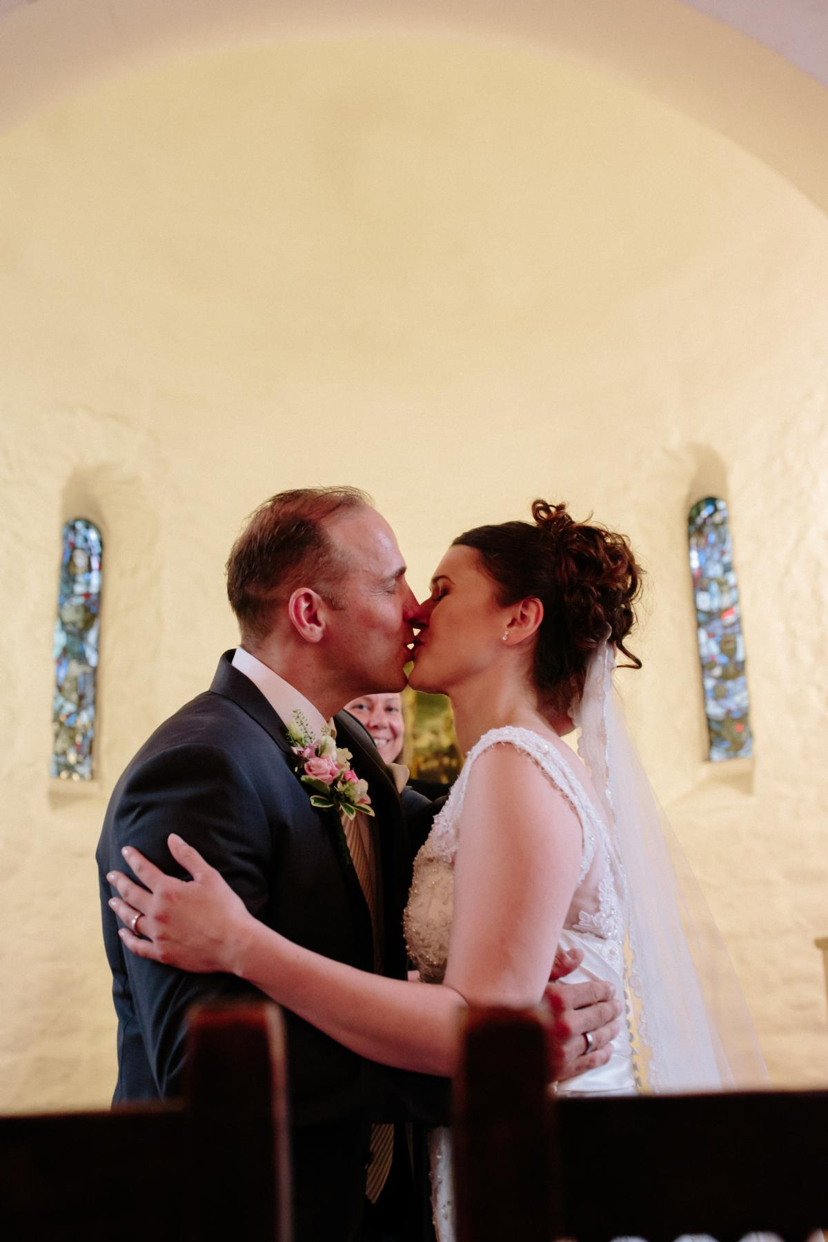 wedding couple kissing in the old village church in Berlin Lankwitz