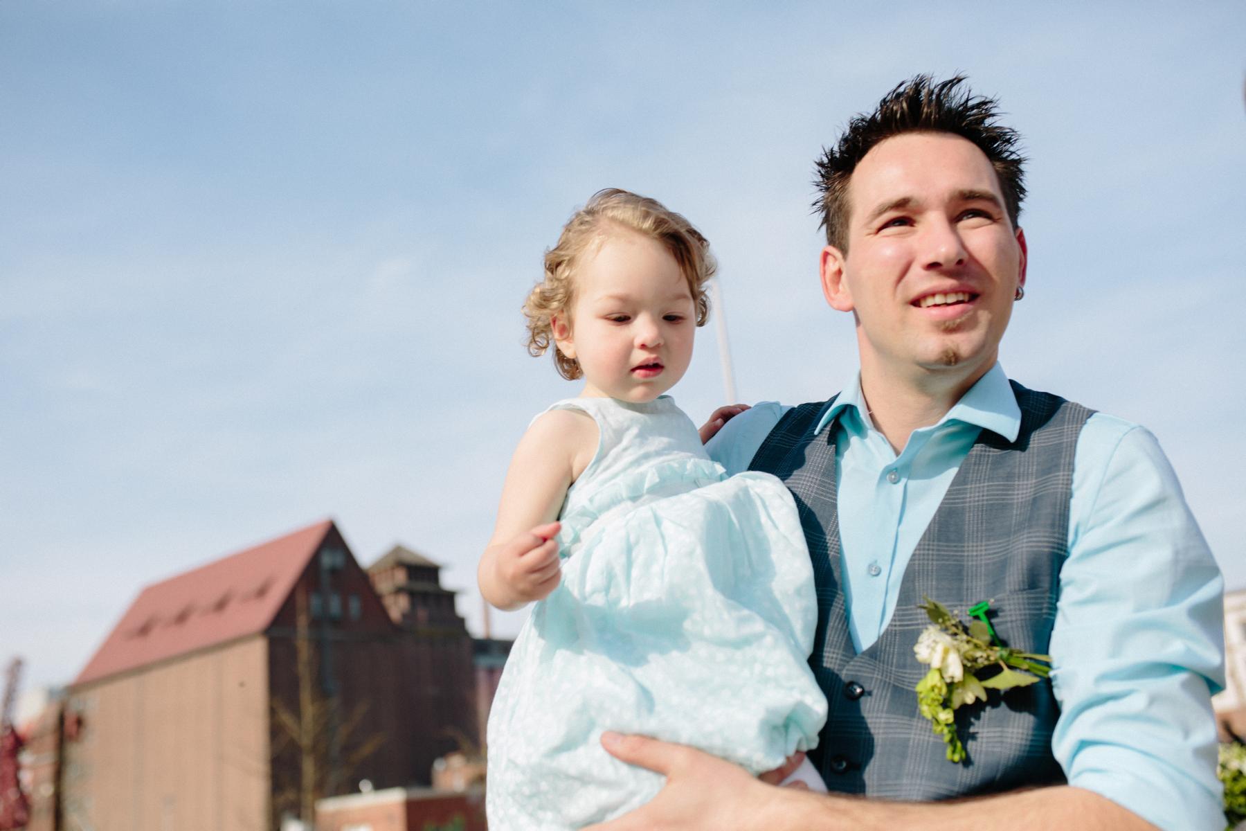 Bräutigam mit Tochter auf dem Arm