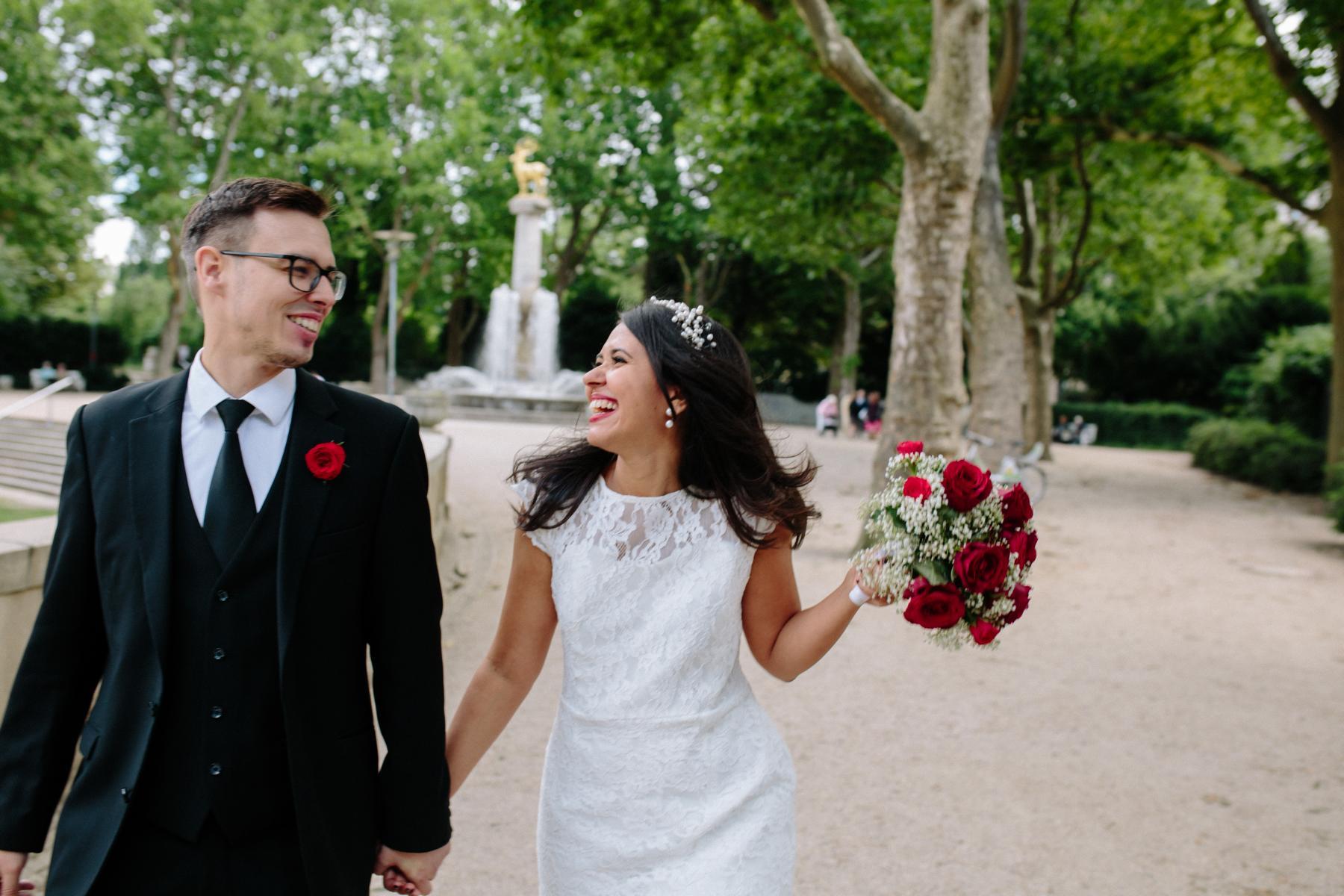 Brautpaar spaziert ausgelassen durch den Park am Rathaus Schöneberg