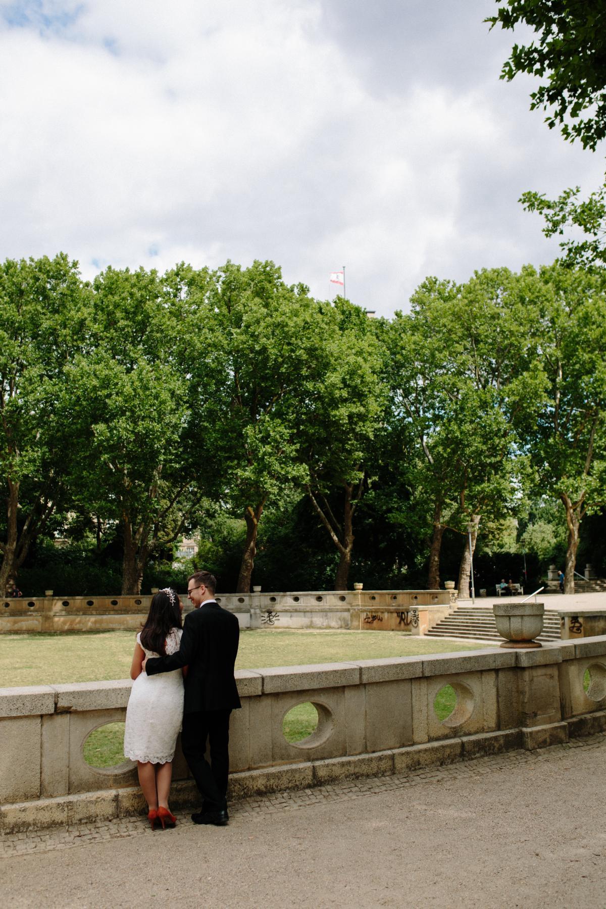 Bräutigam und Braut stehen im Park neben dem Rathaus Schöneberg