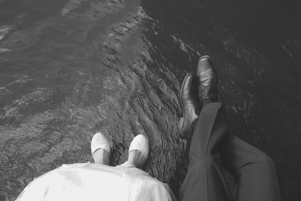 Brautpaar lässt die Füße über dem Wasser des Wandlitzsees baumeln